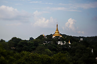 A temple stupa overlooking a green expanse outside of Mandalay in Myanmar.
