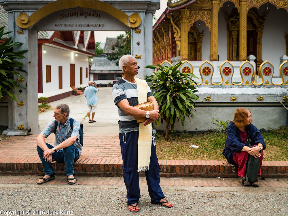 """11 MARCH 2016 - LUANG PRABANG, LAOS:  A Lao man flanked by tourists waits for Buddhist monks to pass him during the morning tak bat in Luang Prabang. Luang Prabang was named a UNESCO World Heritage Site in 1995. The move saved the city's colonial architecture but the explosion of mass tourism has taken a toll on the city's soul. According to one recent study, a small plot of land that sold for $8,000 three years ago now goes for $120,000. Many longtime residents are selling their homes and moving to small developments around the city. The old homes are then converted to guesthouses, restaurants and spas. The city is famous for the morning """"tak bat,"""" or monks' morning alms rounds. Every morning hundreds of Buddhist monks come out before dawn and walk in a silent procession through the city accepting alms from residents. Now, most of the people presenting alms to the monks are tourists, since so many Lao people have moved outside of the city center. About 50,000 people are thought to live in the Luang Prabang area, the city received more than 530,000 tourists in 2014.      PHOTO BY JACK KURTZ"""