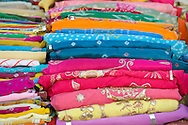 Piles of colourful fabrics for sale in the Sardar Market in Jodhpur, Rajasthan, India