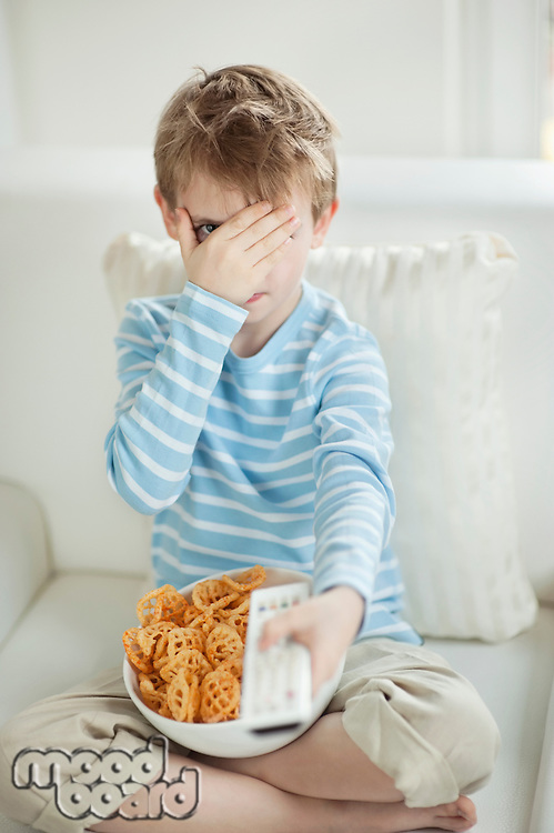 Little boy watching scary movie with a bowl full of wheel shape snack pellets