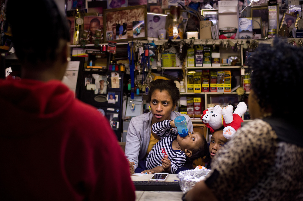 "Kiara Taylor (center) cashiers at the family business, Taylor's Grocery, while she looks after her son, 1-year-old Isaac Taylor, and brother, 6-year-old Claudius Taylor III. She chats about neighborhood news with longtime customer Shamika Johnson (left), at the East Stuart store Jan. 12, 2016. ""I've been coming to this store ever since I could walk,"" said Johnson, who was shopping with her own two children. (XAVIER MASCAREÑAS/TREASURE COAST NEWSPAPERS)"