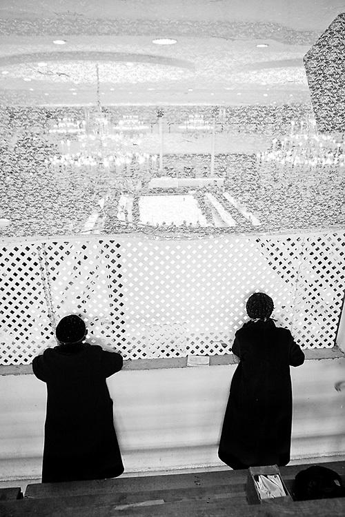 Donne in preghiera  dietro all`inferiata con cui e` coperta la parte delle donne durante la festa Purim, il carnevale ebraico nella sinagoga di New Square, la stessa sinagoga in cui Kal era solito studiare e pregare quando era bambino. Foto scattata il 16 Marzo, 2014.