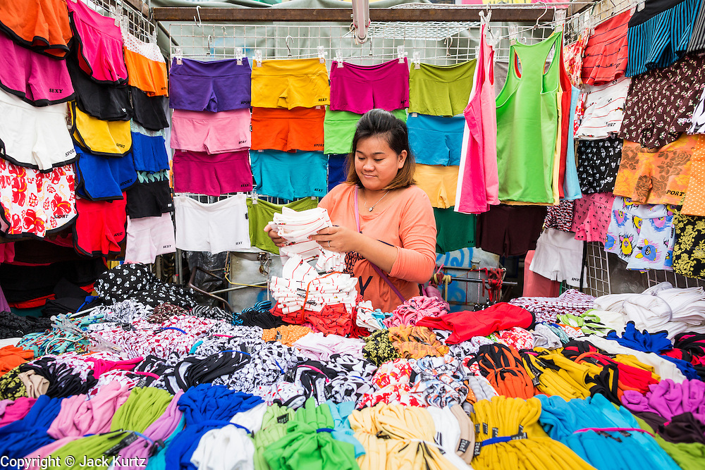 06 JUNE 2013 - BANGKOK, THAILAND:     A clothing vendor sets up her shop in Bobae Market in Bangkok. Bobae Market is a 30 year old market famous for fashion wholesale and is now very popular with exporters from around the world. Bobae Tower is next to the market and  advertises itself as having 1,300 stalls under one roof and claims to be the largest garment wholesale center in Thailand.       PHOTO BY JACK KURTZ