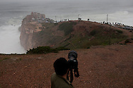 People look on as surfers trie to catch the waves at North Beach during a giant swell that hit the Portuguese coast today. Brazilian surfer Carlos Burle surfed the tallest wave of the day at North Beach, Nazare, Center of Portugal, 28 October 2013. Havaiian Garrett Mcnamara's set the record for the biggest wave ever surfed on January 2013 also at Nazaré. PAULO CUNHA /4SEE
