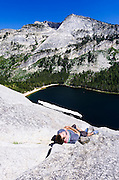 Rock climber relaxing on Stately Pleasure Dome above Tenaya lake, Tuolumne Meadows, Yosemite National Park, California USA