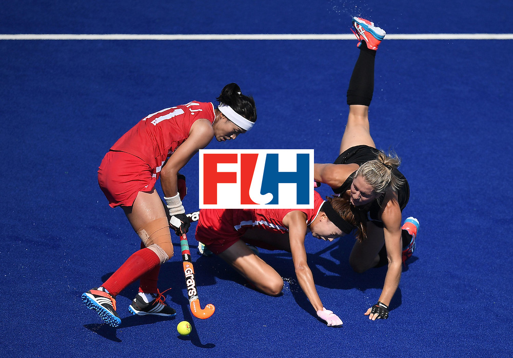 New Zealand's Stacey Michelsen (R) and South Korea's Kim Hyunji (C) collide as South Korea's Kim Jong Eun controls the ball during the womens's field hockey New Zealand vs South Korea match of the Rio 2016 Olympics Games at the Olympic Hockey Centre in Rio de Janeiro on August, 7 2016. / AFP / MANAN VATSYAYANA        (Photo credit should read MANAN VATSYAYANA/AFP/Getty Images)