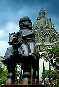 'Man On Horse' sculpture in Plaza Botero by Medellin's native son, Fernando Botero.  Botero is known for his exaggerated forms.  The art nouveau Palace of Culture is seen in the background.