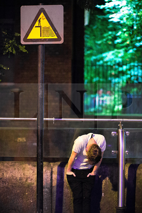 © Licensed to London News Pictures . 26/08/2016 . Manchester , UK . A man slouches against a canalside barrier on Canal Street in Manchester's Gay Village as revellers enjoy a late night during 2016 Manchester Gay Pride Big Weekend . Photo credit : Joel Goodman/LNP