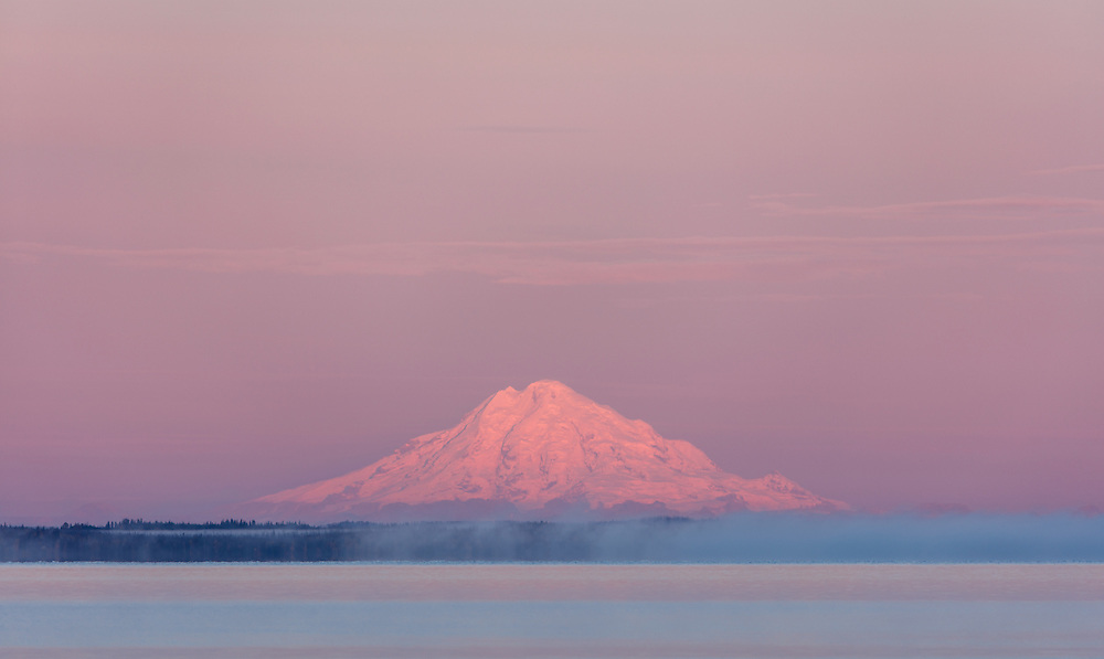 Fog rolls in on Skilak Lake in the Kenai National Wildlife Refuge as sunrise bathes Mount Redoubt with alpenglow in Southcentral Alaska. Autumn. Morning.