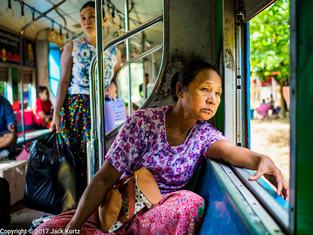 25 NOVEMBER 2017 - YANGON, MYANMAR: A woman looks out the window on the Yangon Circular Train. The Yangon Circular Train is a 45.9-kilometre (28.5 mi) 39-station two track loop system connects satellite towns and suburban areas to downtown. The train was built during the British colonial period, the second track was built in 1954. Trains currently run both directions (clockwise and counter-clockwise) around the city. The trains are the least expensive way to get across Yangon and they are very popular with Yangon's working class. About 100,000 people ride the train every day. A a ticket costs 200 Kyat (about .17¢ US) for the entire 28.5 mile loop.    PHOTO BY JACK KURTZ