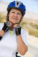 Senior woman adjusting cycling helmet