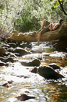 Teenage boy (16-17 years) lying on tree trunk by stream in forest
