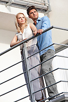Full length of young couple looking away while standing at balcony