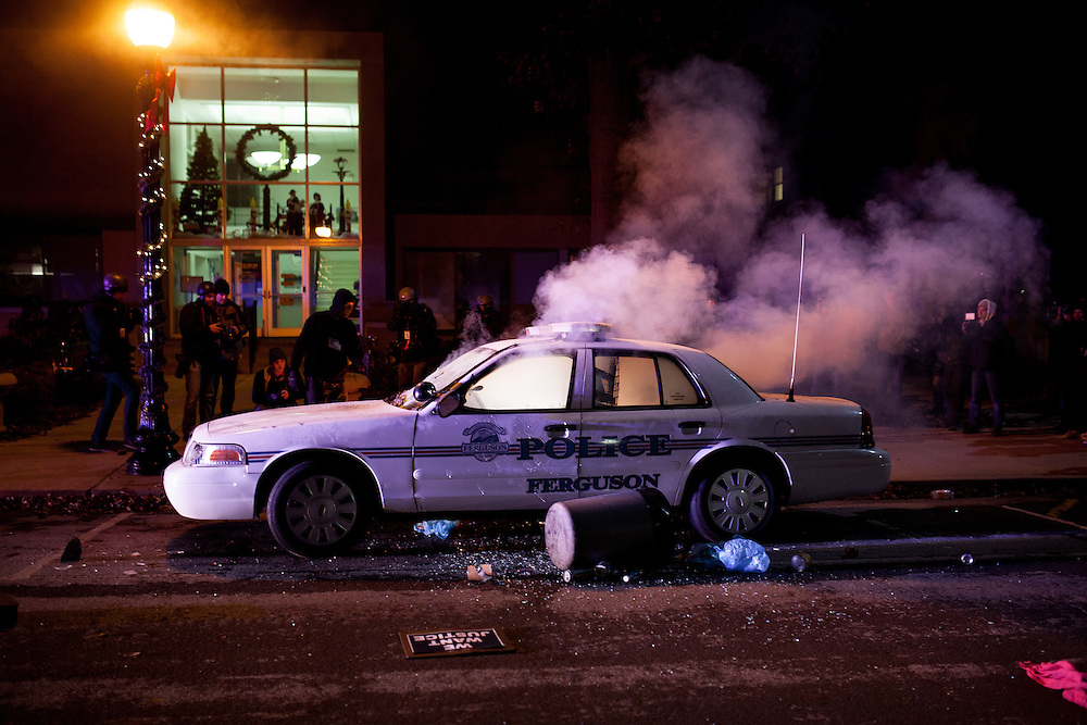 A squad car, set on fire by protestors, burns in front of Ferguson City Hall. Demonstrators took to streets in response to a grand jury failing to indict officer Darren Wilson for the shooting death of Michael Brown Jr.