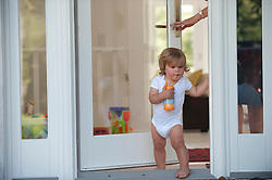 infant boy being let out of the front door of a home