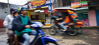 A tricycle and a motorbike on a busy street, Tagbilaran, Bohol, Philippines..