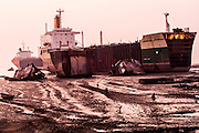 Workers pass in front of Canadian ship on a beach turned into a ship-breaking yard, in Chittagong, Bangladesh, 12th December 2006.<br /> <br /> Chittagong's shipbreaking yards in Bangladesh are the second largest shipbreaking operation in the world after India. At high tide vessels are driven at full speed up onto one of the world's longest and now most polluted beaches. Here, half of the world's supertankers are hacked and torn apart by an army of workers using blowtorches, sledgehammers and plain brute force. The number of accidents and casualties at the yard is believed to be the highest in the region. Workers cut steel plates continuously without eye protection. Many don't wear uniforms, protective gloves or boots. However, Bangladesh is dependent on shipbreaking for its domestic steel requirements and the industry employs, directly or indirectly, an estimated 100,000 Bangladeshis.<br /> <br /> In recent years shipbreaking has become an issue of major environmental concern. <br /> Shipbreaking yards in developing nations like Bangladesh have lax or no environmental controls, enabling large quantities of highly toxic materials to escape into the environment causing serious health problems among shipbreakers and the local population. Environmental campaign groups such as Greenpeace have made the issue a high priority for their campaigns. <br /> PHOTOGRAPH BY SIMON DE TREY-WHITE photographer in delhi