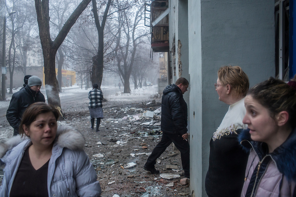 DONETSK, UKRAINE - JANUARY 30, 2015: Residents of an apartment building damaged when a rocket or mortar landed just outside take a break from cleaning up debris in Donetsk, Ukraine. At least two people were killed on the sidewalk when another shell landed just around the corner, and at least five died when a shell landed in the parking lot of a nearby humanitarian aid distribution center. CREDIT: Brendan Hoffman for The New York Times