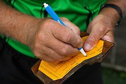 Soccer referee Aubrey Cashman fills out a new score card befoe a soccer match between Lexington Catholic and Henry Clay, Tuesday, Aug. 13, 2013 at Lexington Catholic Soccer/Football Stadium in Lexington. Photo by Jonathan Palmer