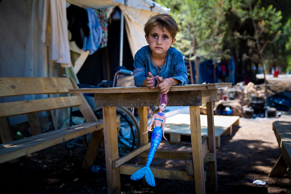 "Najah, 4, a Kurdish Syrian refugee from Aleppo, plays on a table her Grandpa Jameel made, which sits outside of her family's tent in Ritsona refugee camp, an hour north of Athens, Greece. <br /> <br /> extended family have been stranded in Greece since they arrived in March 2016, after the Balkan borders were closed to all refugees. Referring to their extended family, Grandpa Jameel said, ""We are happy to go anywhere, as long as we can stay together."""