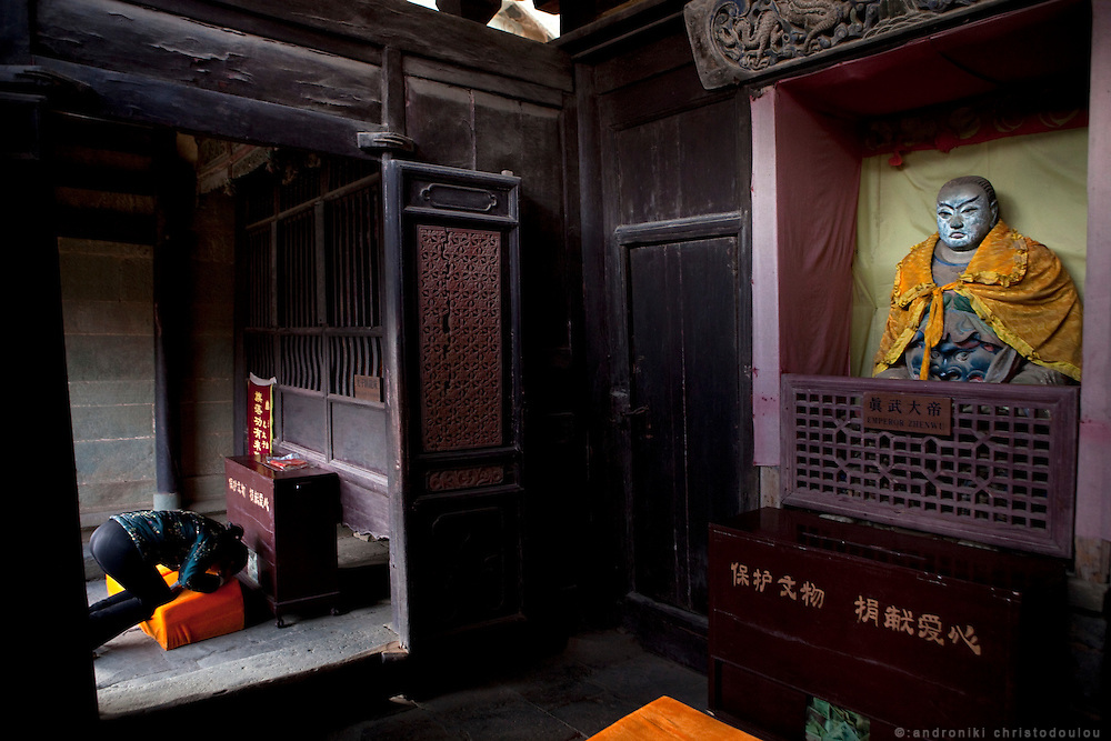 Asia, China, Hubei province.  Woman prayingh at Nanyan Temple on Wudang moutain (Wudang-san), a World Heritage mountain with many Taoist monasteries.