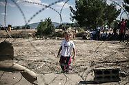 Gevgelija, Macedonia - A little girl next to a fence at the Greek - Macedonian border, on the 23rd of August 2015. Thousands of refugees (mostly coming from Syria) and immigrants try every day to cross the Greek border to Macedonia (Fyrom), hoping to continue their journey to Central/North Europe and eventualy reach countries like Germany, Great Britain and Sweden.