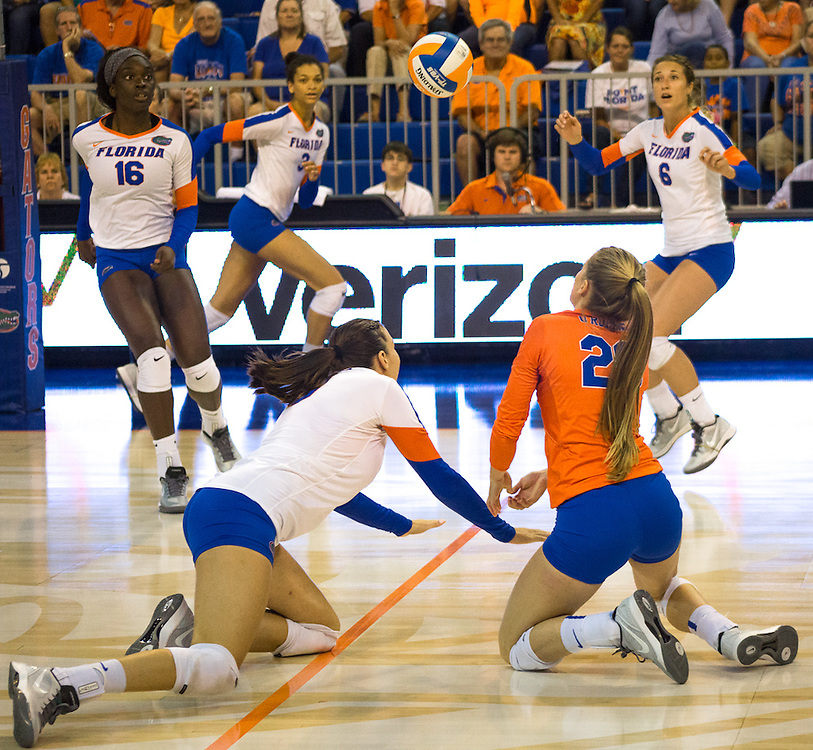 Živa Recek (left) and Nikki O'Rourker dig in an attemp to save the ball from touching the court's floor. (photo by Samuel Navarro)