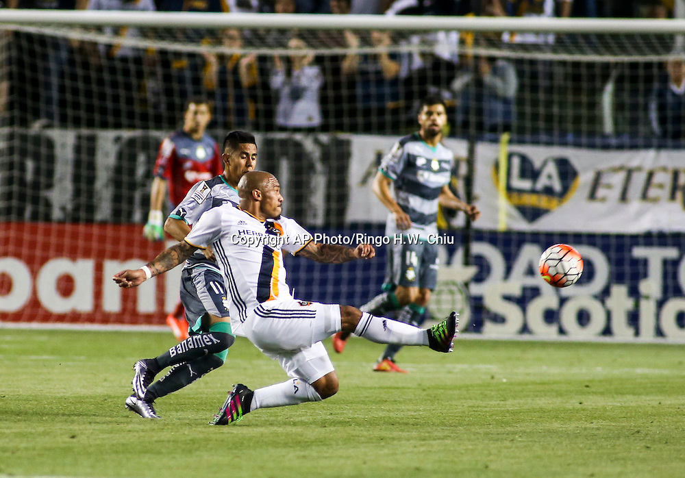 Los Angeles Galaxy's midfielder Nigel de Jong, center, shoots against Santos Laguna during the first half of a CONCACAF Champions League quarter final game in Carson, Calif., Wednesday, Feb. 24, 2016. (AP Photo/Ringo H.W. Chiu)