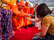 "29 APRIL 2017 - MINNEAPOLIS, MINNESOTA: Thai Buddhist monks bless people during the Songkran Uptown celebration. Several thousand people attended Songkran Uptown on Hennepin Ave in Minneapolis for the city's first celebration of Songkran, the traditional Thai New Year. Events included a Thai parade, a performance of the Ramakien (the Thai version of the Indian Ramayana), a ""Ladyboy"" (drag queen) show, and Thai street food.     PHOTO BY JACK KURTZ"