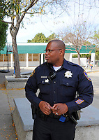 Officer Jeffrey Lofton outside the Hebbron Center, as he keeps a close watch on parents picking up their kids from the bus stop.