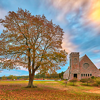 Abandoned Old Stone Church in West Boylston, MA on a beautiful autumn morning at sunrise. This National Historic Site is located on the banks of the Wachusett Reservoir and the beautiful morning light painted this Central Massachusetts historic landmark, oak tree and cloudscape in beautiful hues.<br />