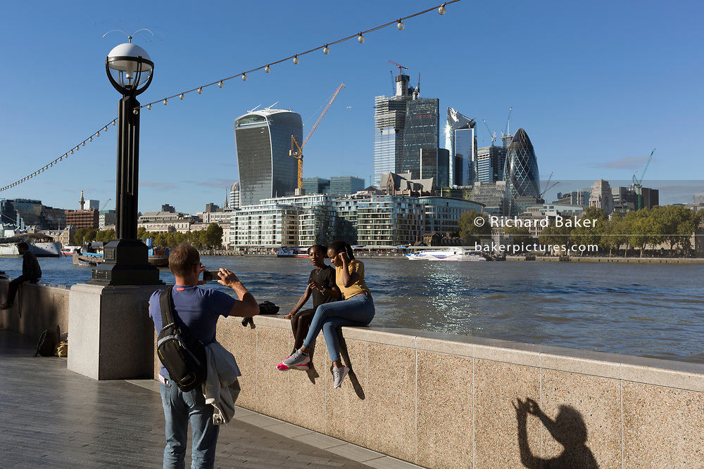 Riverside visitors walk along the Southbank with the City of London skyline (the capital's financial district - aka the Square Mile across the river Thames on the Southbank, on 26th September 2018, in London, England.