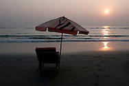 A beach umbrella, decorated with the stripes of a Benal tiger, sits alone as a witness to the setting sun at Cox's Bazar, Bangladesh.
