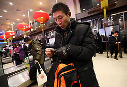 epa05751030 (09/22) Chinese migrant worker Wang Pengfei looks on his ticket as he arrives at the Beijing Railway Station on his journey back to his hometown for the Spring Festival in Beijing, China, 22 January 2017. Wang is the migrant worker and is working in the capital city as a delivery man. He will travel to visit his family in the Shandong Province for the annual Chinese Lunar New Year or Spring Festival. This is the only time he gets to see his family each year. Wang will join millions of fellow Chinese travelers making their way back home as they pack trains, planes and buses, in what is the largest human migration in the world. The journey, known as 'Chunyun' - the annual spring migration, will involve a total of 2,98 billion trips, starting from 13 January and continuing until 21 February 2017.  EPA/HOW HWEE YOUNG PLEASE REFER TO THE ADVISORY NOTICE (epa05751021) FOR FULL PACKAGE TEXT