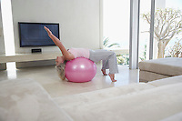 Mature woman stretching using exercise ball in living room