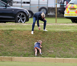 The Queen's granddaughter Zara Tindall rushes to the rescue of her daughter Mia at the Gloucestershire Polo Festival.<br /> <br /> Mia had become detached from the group and had started to cry while holding her cuddly toy. Zara was nearby talking to her sister in law Autumn Phillips and when she saw what had happened she ran down a grass bank to her daughter and scooped her up for a cuddle.<br /> <br />11 June 2017.<br /><br />Please byline: Vantagenews.com<br /><br />UK clients should be aware children's faces may need pixelating.