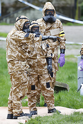 © Licensed to London News Pictures. 24/04/2018. Salisbury, UK. Members of the armed forces remove contaminated soil from the area at the Maltings where a bench was earlier removed the cleanup operation begins in Salisbury. Former Russian Spy Sergei Skripal and his daughter Yulia were poisoned using a nerve agent in the city last month. Experts have warned that 'Toxic levels' of the nerve agent novichok could still be present at hot spots around the city. Photo credit: Peter Macdiarmid/LNP