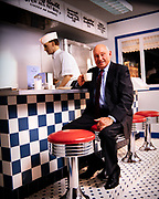 Samuel Truett Cathy (March 14, 1921 – September 8, 2014) was an American businessman, investor, author, and philanthropist. He founded the fast food restaurant chain Chick-fil-A. Cathy is sitting in a recreation of the cafe counter from his first restaurant - The Dwarf House - which is a part of the Chick-fil-A corporate headquarters south of Atlanta, GA.