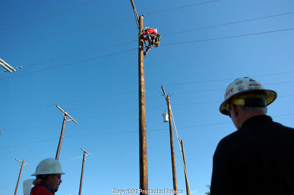 Jodi Miller Lubbock Avalanche-Journal.A lineman started his descent down a 40 foot utility pole Saturday as his teamates look on during the 17th annual LIneman's Rodeo competition.