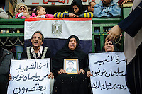 During demonstrations against the Mubarak regime in Tahrir Square, the family of a young man killed more than two weeks earlier at the start of the protest hold his picture and two signs. The father holds a sign which says THE FAMILY OF MARTYR MOHAMED SOLIMAN PROTEST. The second sign reads THE FAMILY OF MARTYR MOHAMED SOLIMAN DEMAND MUBARAK GO. (Cairo, Egypt - February 11, 2011)