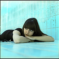 A teenage girl lying on the floor of a swimming pool