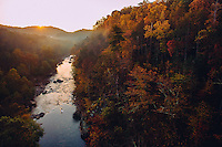 Man standup paddle boarding on the Roanoke River in the Blueridge Mountains at sunrise at height of fall color