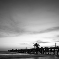 Orange County California San Clemente pier at sunset black and white photo. Orange County is an affluent area of Southern California in the Western USA. Photo is high resolution. Copyright ⓒ 2017 Paul Velgos with All Rights Reserved.