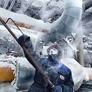 Russian workers at Achimgaz's UKPG gas and condensate processing system spray steam to unfrozen pipes in Novy Urengoi, Arctic Siberia, Russia. Achimgaz is a joint-venture between Germany's BASF Wintershall and Russia's Gazprom. Photo by photographer Justin Jin.