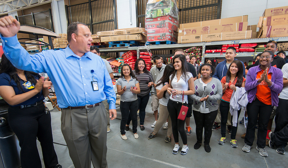 Walmart regional manager Todd Manley leads his team and Scarborough High School students in the Walmart cheer, May 22, 2014.