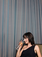 Woman drinking champagne in front of curtains indoors