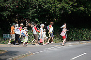 Photo by Andrew Tobin/Tobinators Ltd - 07710 761829 - Competitors make their way from the local pub to the competition ground before the World Peashooting Championships held at Witcham, Cambridgeshire, UK on 13th July 2013. Run in conjunction with the village fair, the Championships have been held in Witcham since 1971 when they were started by a Mr Tyson, the village schoolmaster, in order to raise funds for the village hall.Competitors come from as far afield as the USA and New Zealand to attempt to win the event. The latest technology is often used, including laser sights and titanium and carbon fibre peashooters. All peashooters must conform to strict length rules, not exceeding 12 inches, and have to hit a target 12 feet away. Shooting 5 peas at a plasticine target attached to a hay bale, the highest scorers move through the initial rounds to a knockout competition, followed by a sudden death 10-pea shootout.