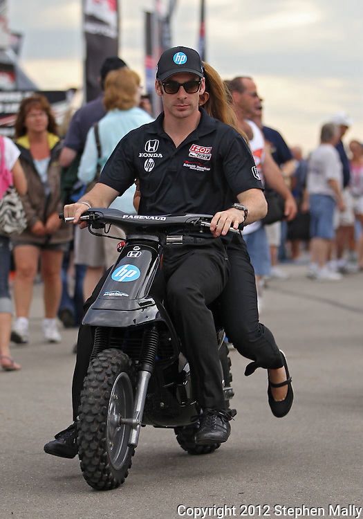 Simon Pagenaud leaves an autograph session on a motorbike before the start of the IZOD IndyCar Iowa Corn Indy 250 auto race at the Iowa Speedway in Newton, Iowa on Saturday, June 23, 2012.