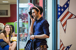 © Licensed to London News Pictures . Manchester , UK . 05/04/2015 . A man wearing pink rabbit ears outside a takeaway in Manchester City Centre . Revellers on a Saturday night out during the Easter Bank Holiday weekend . Photo credit : Joel Goodman/LNP