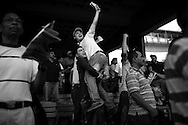 In this photo taken Dec. 4, 2010, fans celebrate while watching a horse race during the Caribbean Classic Series at the Rinconada racetrack in Caracas, Venezuela.